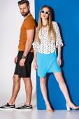módní mladý pár pózuje v letních šatech a slunečních brýlích na šedé a modré