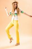 gyönyörű divatos lány pózol sárga nadrágban, póló és szalma kalap bézs