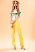 Stylisches Mädchen posiert in gelber Hose, Polo und Strohhut auf beige