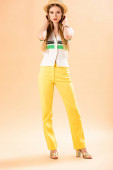 atraktivní stylová žena pózující ve žlutých kalhotách, polo a slamáku na béžové