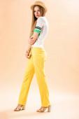 stylová mladá žena pózující ve žlutých kalhotách, polo a slamáku na béžové