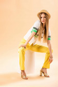 fashionable young woman in yellow trousers, polo and straw hat sitting on white cube on beige