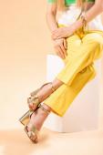 oříznutý pohled na módní dívku ve žlutých kalhotách a podpatcích sandálech sedících na bílé kostce na béžové