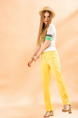 Fotografie stylish young woman posing in yellow trousers, polo and straw hat on beige