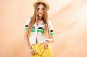 krásná elegantní mladá žena pózující ve žlutých kalhotách, pólo a slamák na béžové