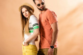 Fotografie beautiful stylish couple posing in summer clothes, straw hat and sunglasses on beige