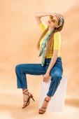 módní blondýnka v džínách, žlutém tričku, slunečních brýlích, podpatcích sandálech a hedvábném šátku sedícím na bílé kostce na béžové