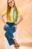 krásná blondýnka v džínách, žluté tričko, sluneční brýle, podpatky sandály a hedvábný šátek sedí na bílé kostce na béžové