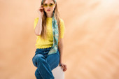 fashionable girl in jeans, yellow t-shirt, sunglasses and silk scarf sitting on white cube on beige