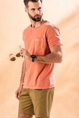 Handsome stylish man posing in shorts and summer t-shirt holding sunglasses on beige stock vector