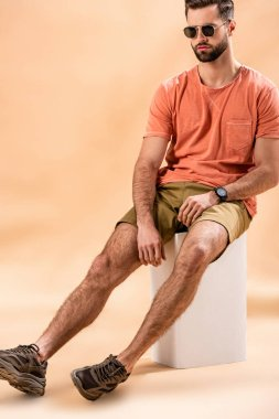Young man in shorts, summer t-shirt and sunglasses sitting on white cube on beige stock vector