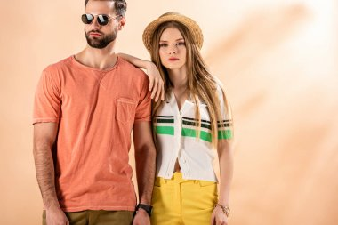 young stylish couple posing in summer clothes, straw hat and sunglasses on beige
