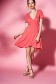 módní dívka pózuje v letních šatech a podpatky sandály na růžové
