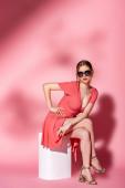 attraktives Mädchen in Sommerkleid und Sonnenbrille sitzt auf weißem Würfel auf rosa