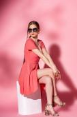 stylová dívka v letních šatech a sluneční brýle sedí na bílé kostce na růžové