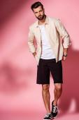 módní muž pózuje v letní košili a šortky na růžové