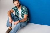 stílusos fiatalember pózol nyári ruhák és napszemüveg szürke és kék