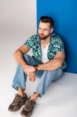 divatos fiatalember pózol nyári ruhák és napszemüveg szürke és kék