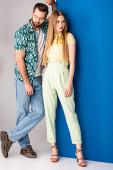 krásný módní pár pózující v letních šatech na šedé a modré