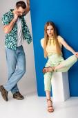 krásný stylový pár pózující v letním oblečení na šedé a modré