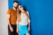 krásný pár pózuje v letních šatech a slunečních brýlích na šedé a modré