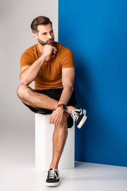 Pensive bearded man in shorts and brown polo sitting on white cube on grey and blue stock vector