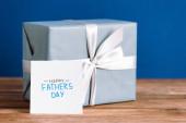 selektivní zaměření pohlednice s nápisem den šťastných otců a dárková krabička s bílým lukem izolované na modré