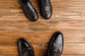 Photo Top view of mens and childrens black classic shoes on wooden background, fathers day concept
