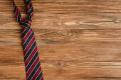 Horní pohled na pánské pruhované kravaty na dřevěném pozadí