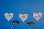 Top kilátás dekoratív karton hamis bajusz és papír vágott szürke szív felirattal boldog apa nap kék háttér