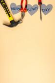 top view kalapács, csavarhúzó, fogó és szürke papír szív felirattal boldog apák napja bézs alapon