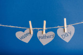 Grey heart-shaped greeting cards hanging on rope with clothespins isolated on blue