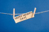 Beige paper greeting card with black lettering happy fathers day hanging on rope with clothespins isolated on blue