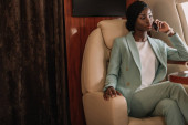 young, confident african american businesswoman talking on smartphone in private jet