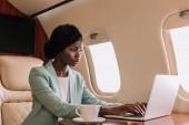 atraktivní, sebevědomá africká americká podnikatelka pracující na notebooku v soukromém tryskáči