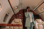 mladá, sebevědomá africká americká podnikatelka mluví na smartphone, zatímco stojí v soukromém tryskáči