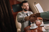 cropped view of african american businesswoman shaking hands with handsome businessman in plane