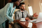 Photo serious businessman pointing with finger at laptop near african american businesswoman