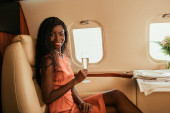attractive african american woman hoding glass of champagne and smiling at camera while sitting near served table in private plane
