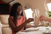 oříznutý pohled na muže cinkání sklenice šampaňského se šťastnou africkou Američankou v soukromém letadle