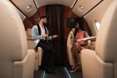 selective focus of elegant interracial couple talking in private jet while holding champagne glasses