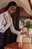 smiling african american stewardess waving hand at camera while putting flowers on table in private jet