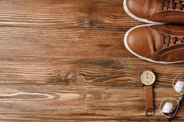 Top view of mens brown casual shoes, wristwatch and glasses on wooden background stock vector
