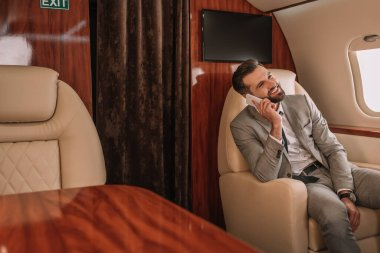 Smiling businessman talking on smartphone while traveling in private jet stock vector