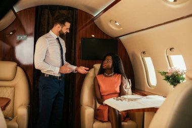 selective focus of handsome air stewards standing with open arms near attractive african american woman in private jet