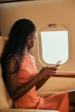 Attractive african american woman chatting on smartphone in private jet stock vector