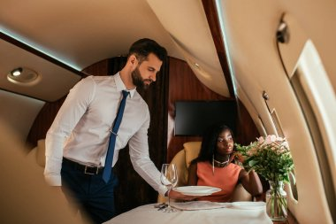 selective focus of handsome air steward serving table near elegant african american woman in plane
