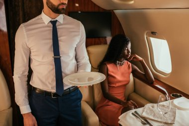 cropped view of air steward holding plates near pensive african american woman sitting at served table in plane