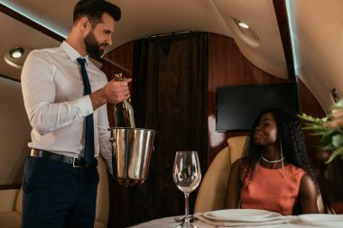 handsome air steward holding champagne bucket and bottle near attractive african american woman in private jet