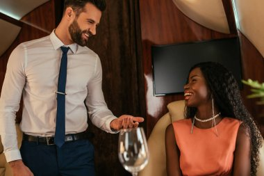 selective focus of smiling air steward looking at happy, elegant african american woman in private plane